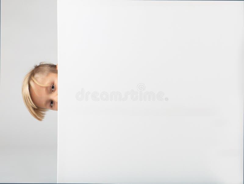 Pouco menino louro que esconde atrás de um cartaz com espaço da cópia fotos de stock royalty free