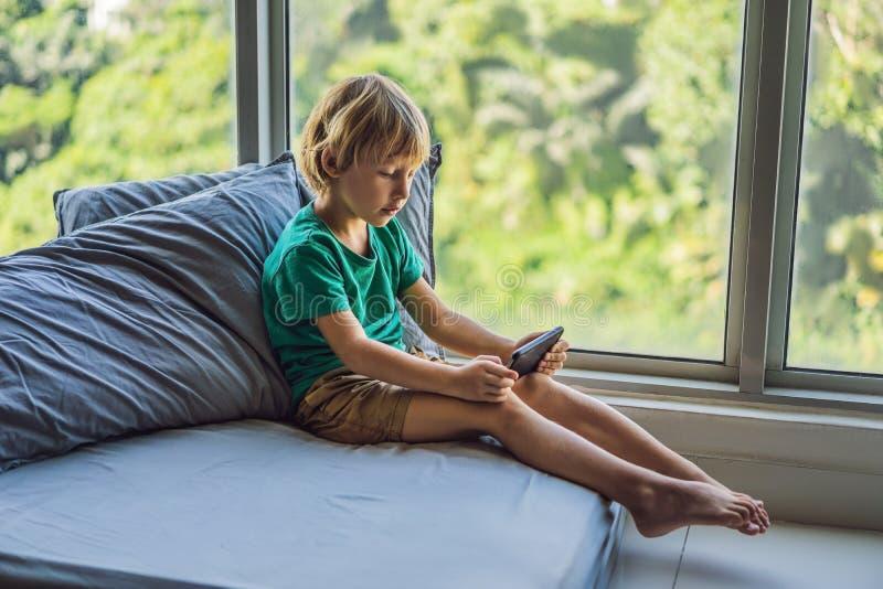Pouco menino louro que joga jogos no smartphone foto de stock