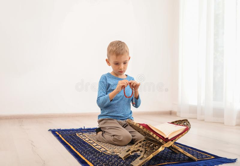 Pouco menino muçulmano com misbaha e rezar do Alcorão imagem de stock