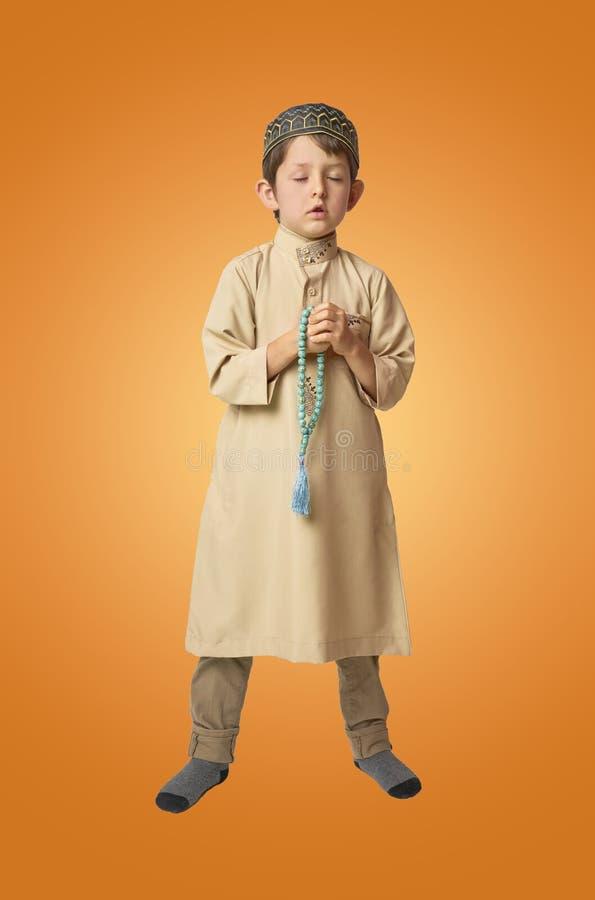 Pouco menino muçulmano que reza e que guarda grânulos de oração no fundo colorido imagem de stock royalty free