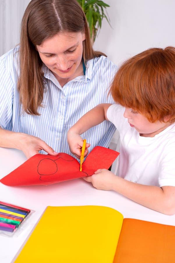 Pouco menino ruivo com um baby-sitter ou uma mãe ou professor senta-se na tabela na sala e corta-se do papel colorido com tesoura fotografia de stock