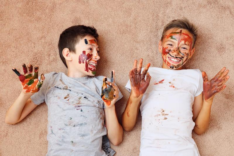 Pouco meninos alegres com pintura na cara e nas mãos que encontram-se no assoalho e no riso imagem de stock royalty free