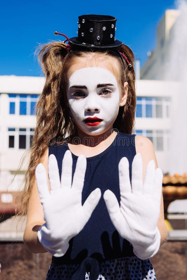 Pouco mimica a pantomima das mostras da menina na rua foto de stock royalty free