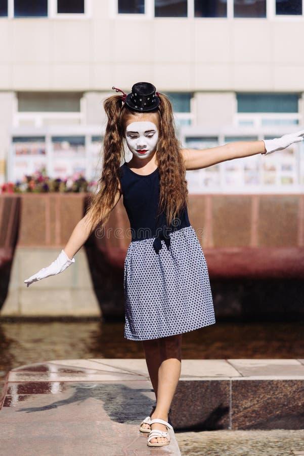 Pouco mimica a pantomima das mostras da menina na rua fotos de stock royalty free