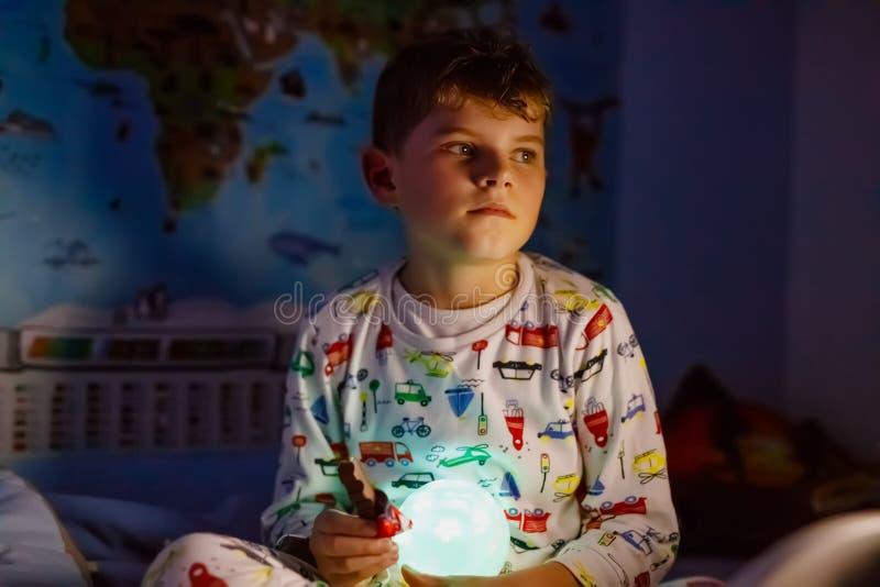Pouco nightwear vestindo do menino pré-escolar da criança que não dorme na cama com lâmpada colorida Aluno saudável que sonha e fotografia de stock