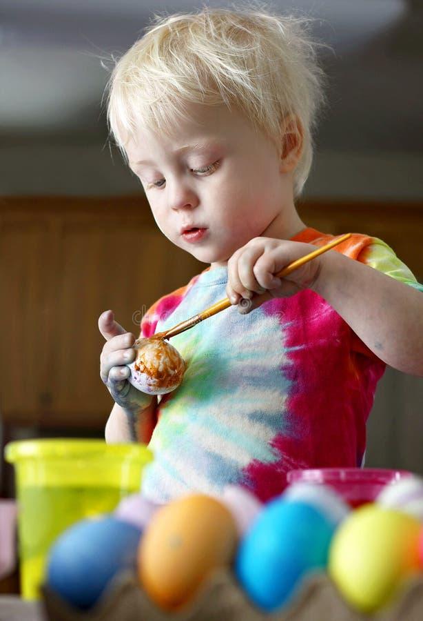 Pouco ovos da páscoa de pintura do menino da criança da criança de dois anos imagem de stock royalty free