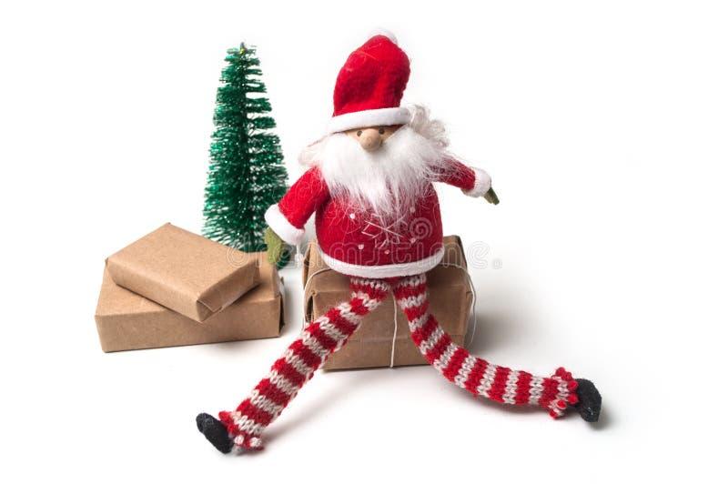 pouco Papai Noel que senta-se em presentes no backgrou branco imagens de stock
