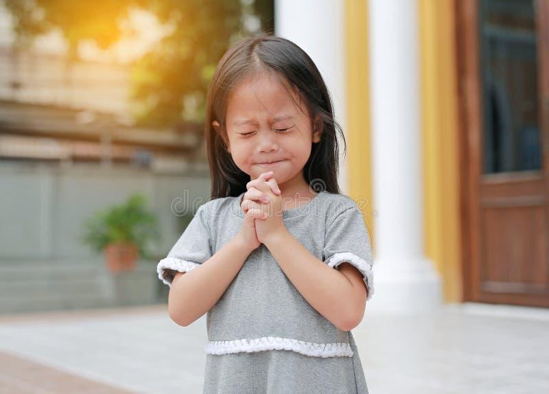 Pouco posição asiática da menina que reza no jardim na manhã A mão que reza, mãos da menina da criança dobrou-se no conceito da o imagens de stock royalty free