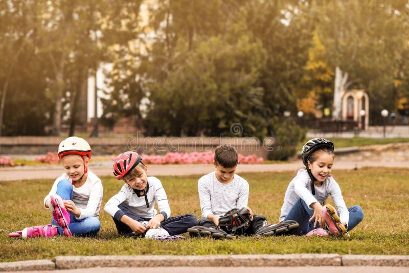 Pouco skateres do rolo que sentam-se na grama imagem de stock