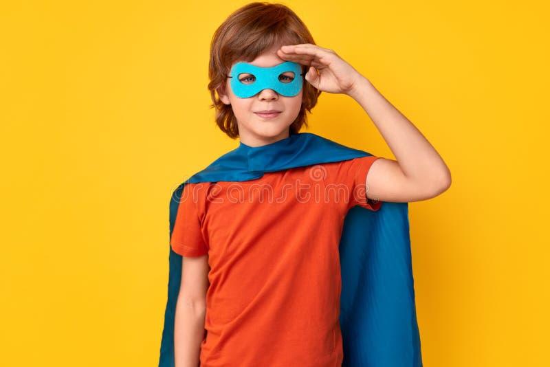 Pouco super-herói que sauda para a câmera fotos de stock royalty free