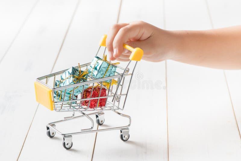 Pouco toque da mão no carrinho de compras com presente pequeno fotos de stock