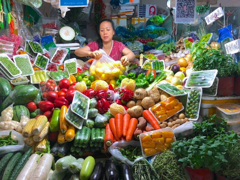 Pouco vegetais está a loja com o proprietário da mulher da loja imagem de stock