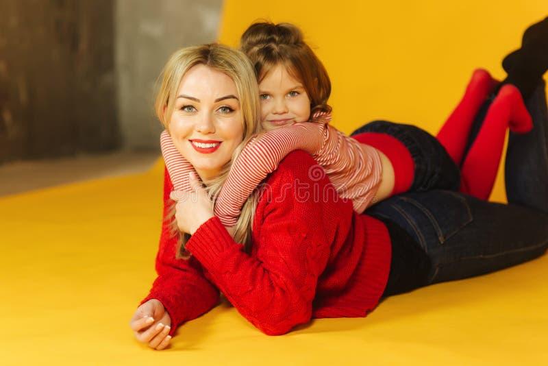 Pouco velho de cinco anos da filha com sua mamã nova A menina coloca na parte traseira da minha mãe Fundo amarelo foto de stock royalty free