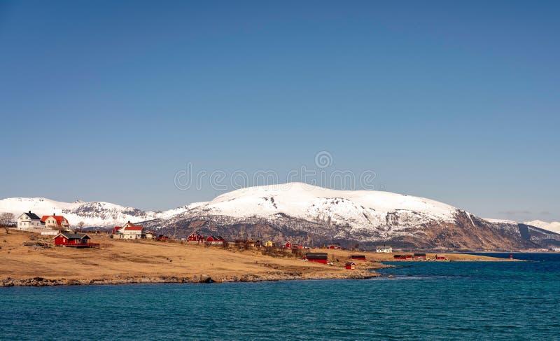 Pouco vila em Noruega do norte no tempo agradável, com céu azul e picos cobertos de neve fotografia de stock royalty free
