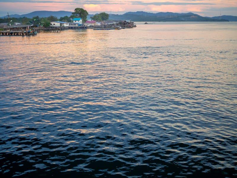 Pouco vila perto do mar no por do sol foto de stock