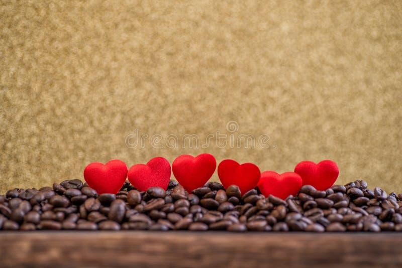 Poucos corações vermelhos do cetim com letras em feijões de café com fundo do ouro, dia de Valentim ou comemoração do dia do casa imagens de stock