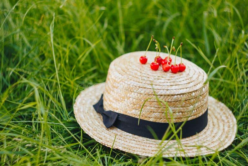 Poucos frutos maduros da cereja doce com o galho no chap?u de palha que encontra-se no ar livre da grama Piquenique na natureza n imagens de stock royalty free