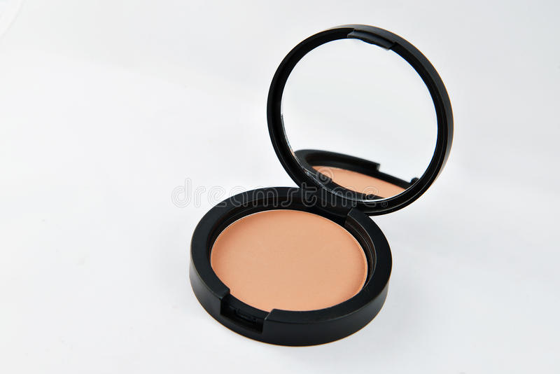 Poudre compacte pour le visage, dans une boîte ronde noire avec le miroir images libres de droits