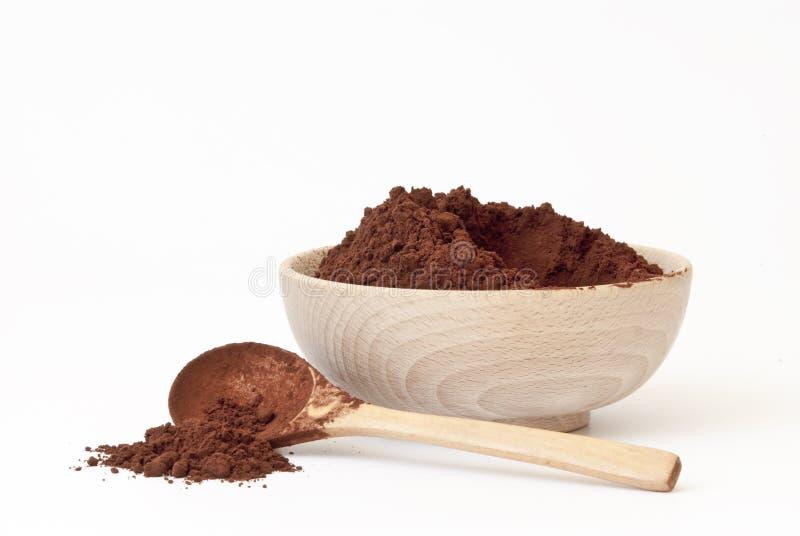 Poudre de cacao dans la cuvette en bois avec la cuillère en bois photos stock