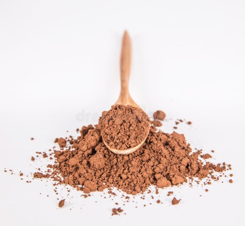 Poudre de cacao et cuillère en bois sur le blanc photos stock