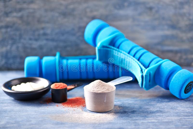 Poudre de créatine, scoop des capsules de protéine de lactalbumine, de taurine et des haltères bleues à l'arrière-plan Nutrition  photographie stock