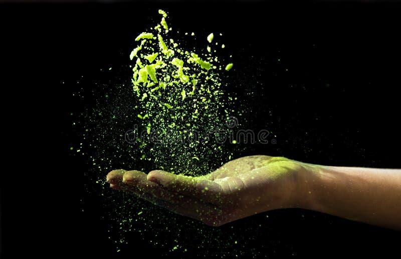 Poudre jaune de holi laissée tomber chez la main de la femme sur le noir images stock