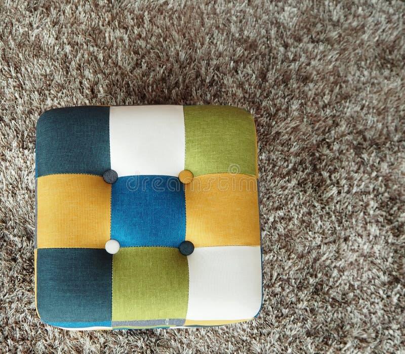Pouf de tissu de quatre couleurs sur un fond gris de tapis photographie stock libre de droits
