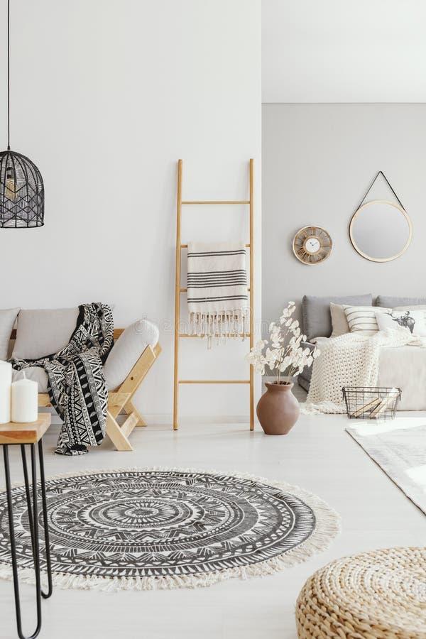 Pouf et couverture ronde dans l'intérieur lumineux de salon avec l'échelle à côté du divan en bois photographie stock libre de droits