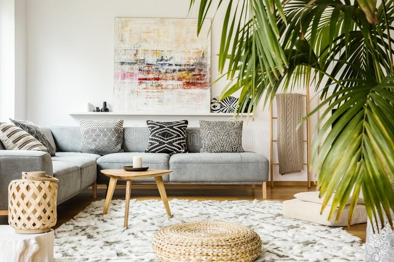 Pouf et table en bois dans le salon moderne avec la peinture ci-dessus images stock