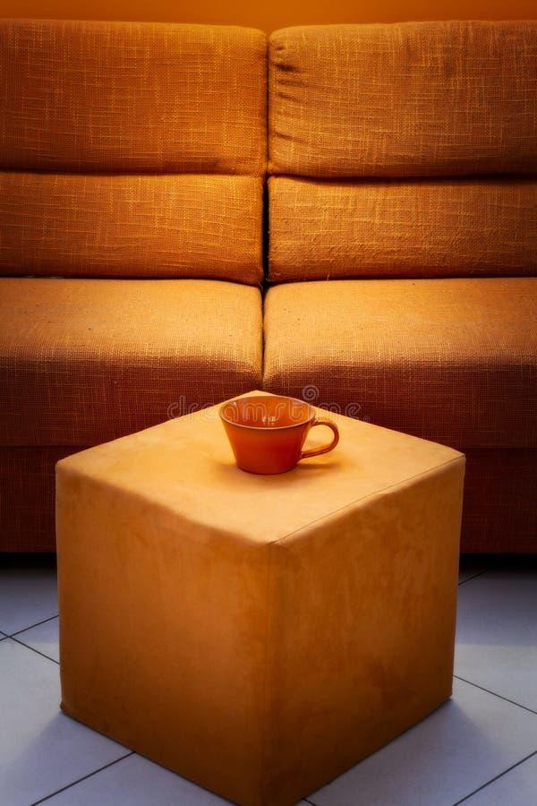 Pouf et tasse oranges de sofa image libre de droits