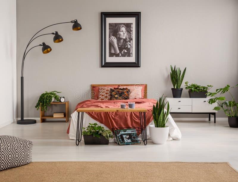 Pouf sur le tapis et les usines devant le lit rouge dans l'intérieur gris de chambre à coucher avec l'affiche et la lampe photographie stock libre de droits
