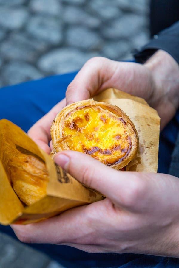 Poul portugaise d'oeufs de dessert (Pasteis de Nata) dans la main de l'homme, plan rapproché photo stock