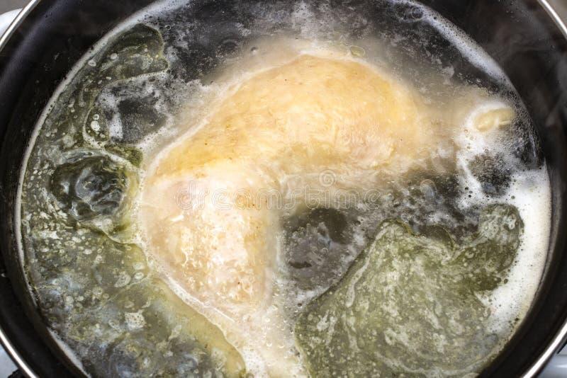 Poulet bouilli dans un plan rapproché de bouillon de pot avec le fond et l'avant brouillés photographie stock libre de droits