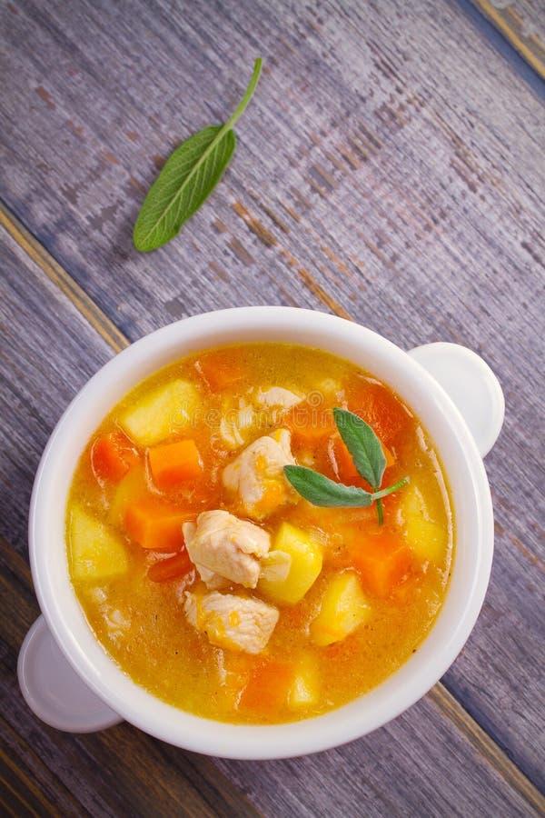 Poulet, courge de butternut, pomme, gingembre et ragoût sage dans la cuvette blanche sur la table en bois Soupe à potiron avec le photo stock