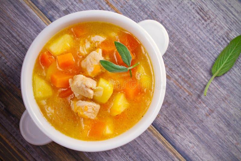 Poulet, courge de butternut, pomme, gingembre et ragoût sage dans la cuvette blanche sur la table en bois Soupe à potiron avec le photographie stock