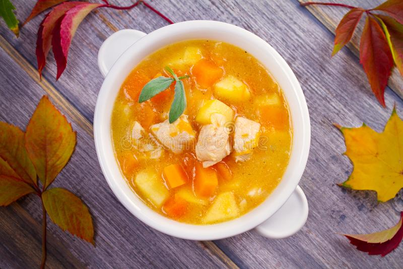 Poulet, courge de butternut, pomme, gingembre et ragoût sage dans la cuvette blanche sur la table en bois Soupe à potiron avec le photos stock
