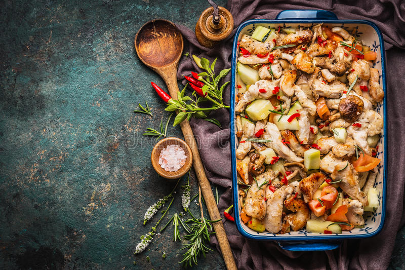 Poulet cuit au four avec des légumes dans la cocotte en terre avec la cuillère en bois et les herbes et les épices fraîches photos libres de droits