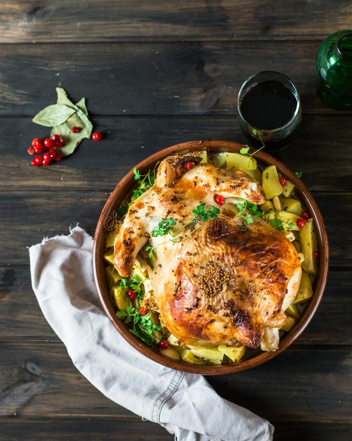 Poulet cuit au four entier avec des champignons et des pommes de terre dans un plat de cuisson sur une table Dinde cuite au four  image libre de droits