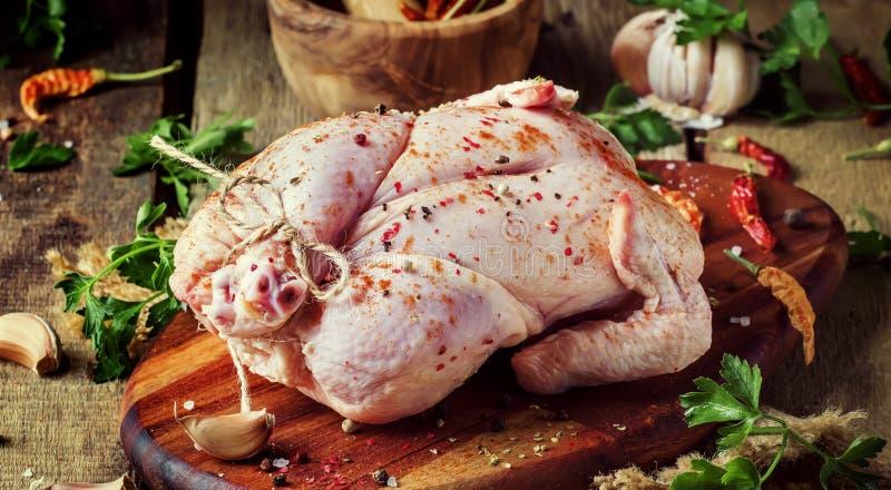 Poulet entier cru avec les épices et la marinade, fond gris, dessus photo libre de droits
