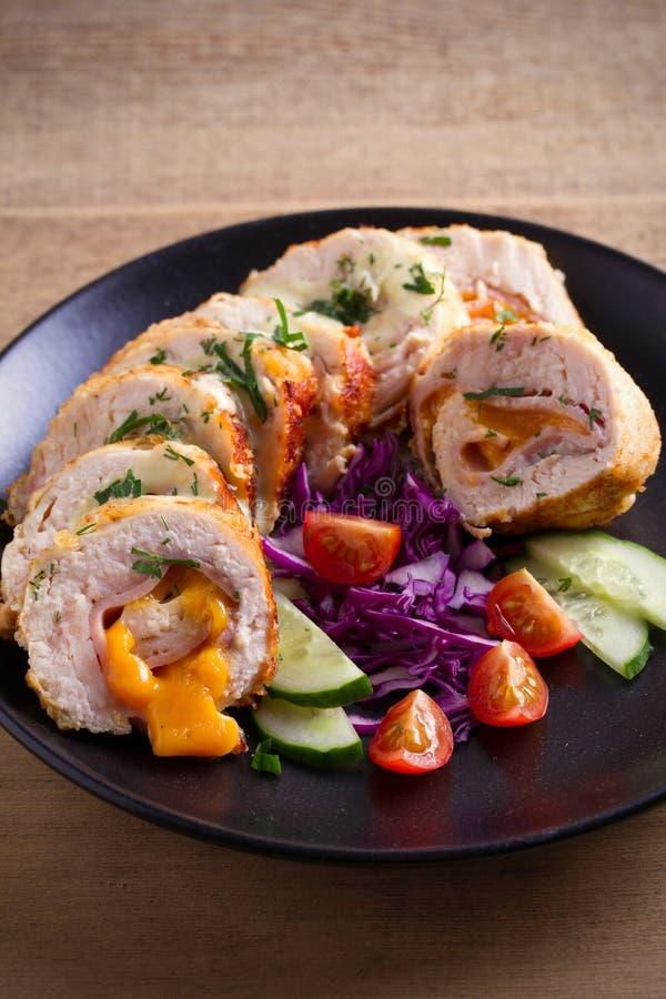 Poulet enveloppé avec du fromage de jambon et de cheddar ; légumes dans le plat noir sur la table en bois photos libres de droits