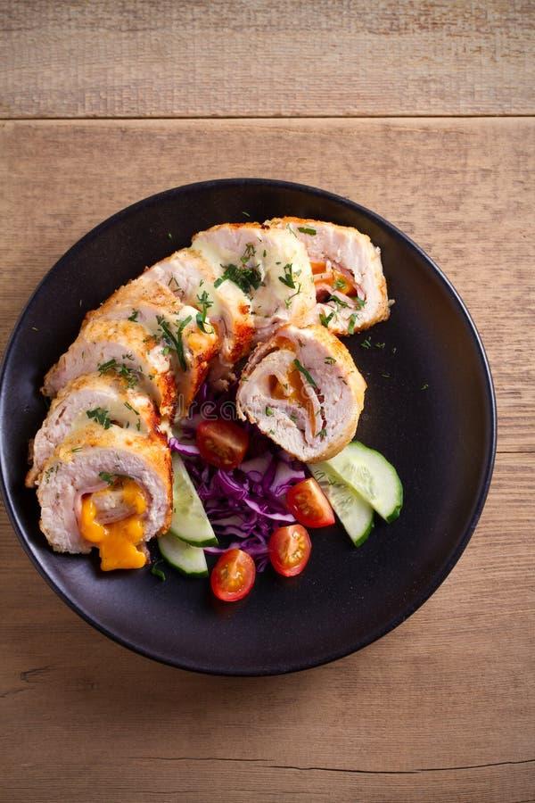 Poulet enveloppé avec du fromage de jambon et de cheddar ; légumes dans le plat noir sur la table en bois photographie stock libre de droits