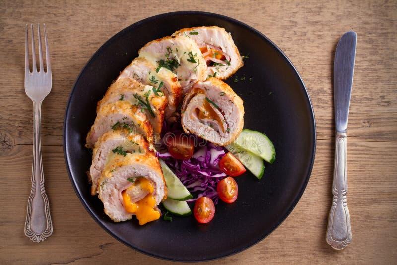 Poulet enveloppé avec du fromage de jambon et de cheddar ; légumes dans le plat noir sur la table en bois image stock