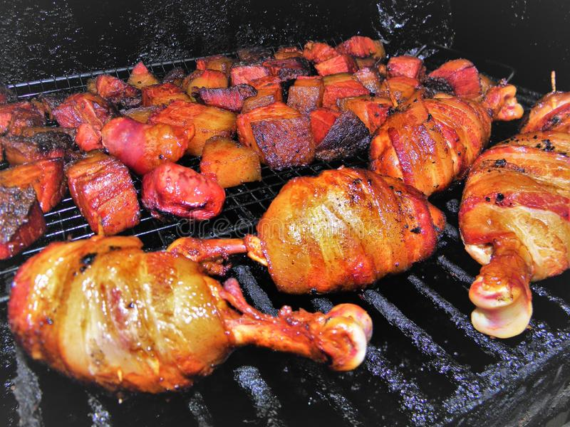 Poulet enveloppé par lard Drumbsticks et extrémités brûlées sur le gril photo libre de droits