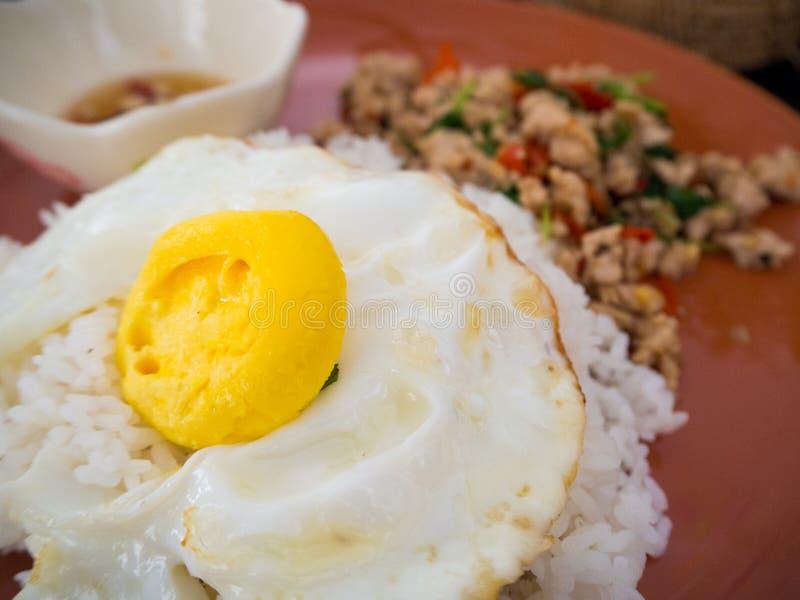 Poulet et oeuf au plat sur le plat de basilic avec du riz image stock