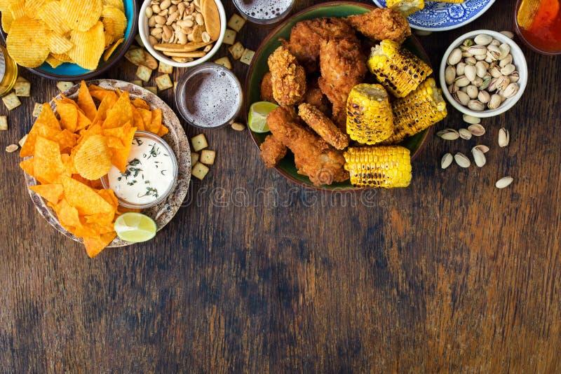Poulet frit, bière, sauces, pommes chips, nachos, arachides, pist photo libre de droits