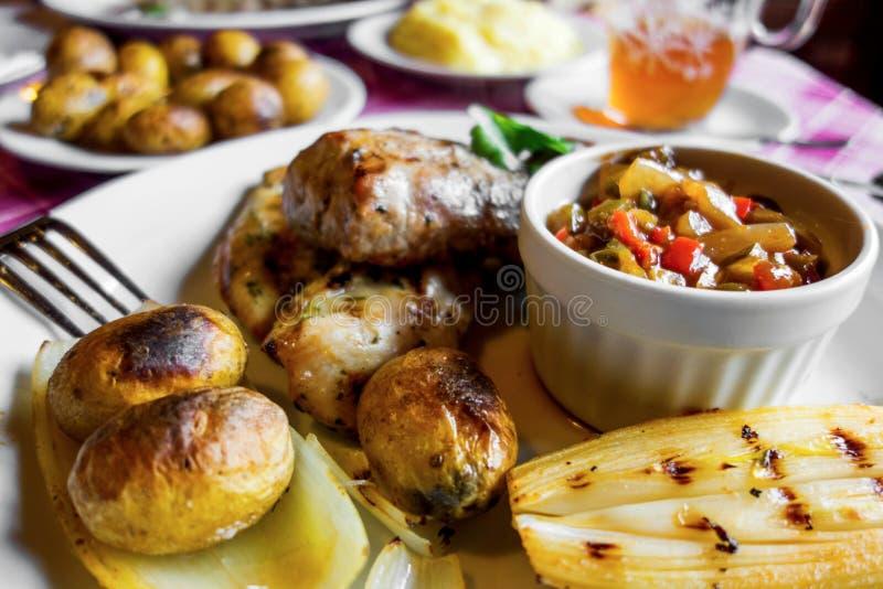 Poulet frit et viande de porc, pomme de terre, légume, chicorée sur la table de restaurant photos stock