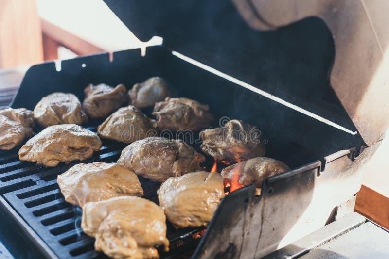 poulet grillé à un pique-nique L'homme a étendu le poulet dans la marinade sur le gril pour sa préparation Grandes carcasses enti photos stock