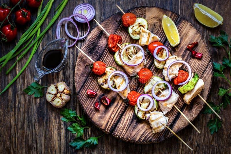 Poulet grillé avec la courgette, les tomates, les oignons et les herbes sur le fond en bois images libres de droits