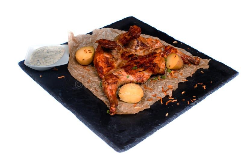 Poulet grillé avec les pommes de terre et la sauce blanche sur un conseil noir sur le fond blanc d'isolement photos libres de droits