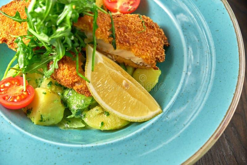Poulet pané avec des légumes et des herbes d'un plat bleu Fond en bois fonc? Patte de poulet frit photo libre de droits